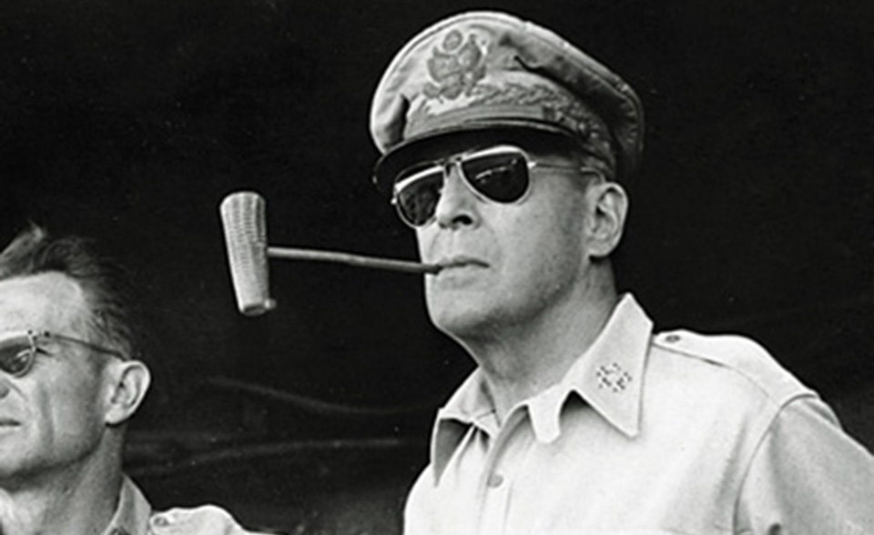 ** FILE ** Five star Gen. Douglas MacArthur smokes one of his trademark corn cob pipes aboard a ship bound for Luzon Island in the Philippines in this Jan. 20, 1945 file photo. A congressional committee cut Gen. MacArthur down to size in 1951, deftly exposing the flaws that had led President Harry Truman to remove him as Korean war commander. The man at left is unidentified. (AP Photo/File)