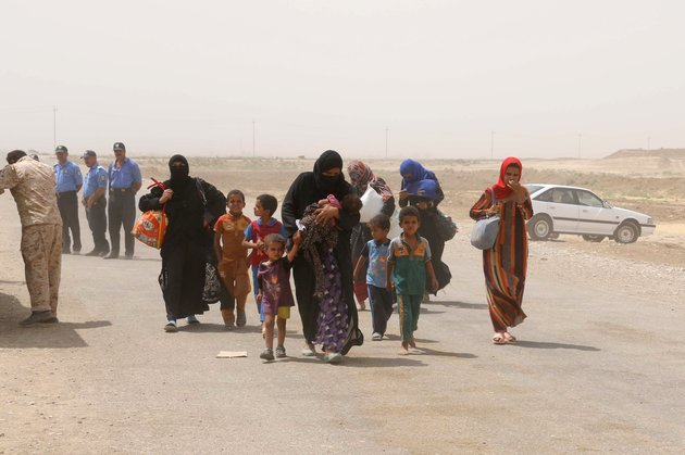 Iraqi families displaced from the areas of Hawija and Hamrin in northern Iraq, due to the advance of the Islamic State jihadist group, arrive in the Kirkuk governorate in search for safety, on August 31, 2015. Since 2014, tens of thousands of Iraqis have been fleeing their hometowns after the Islamic State jihadist group launched an onslaught that overran large areas and brought the country to the brink of breakup. AFP PHOTO / MARWAN IBRAHIM (Photo credit should read MARWAN IBRAHIM/AFP/Getty Images)